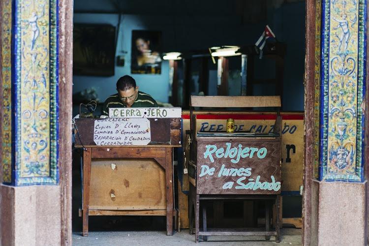 Havana, Cuba - September 7, 2014: A man working in a watch repair shop in the streets of Havana, Cuba
